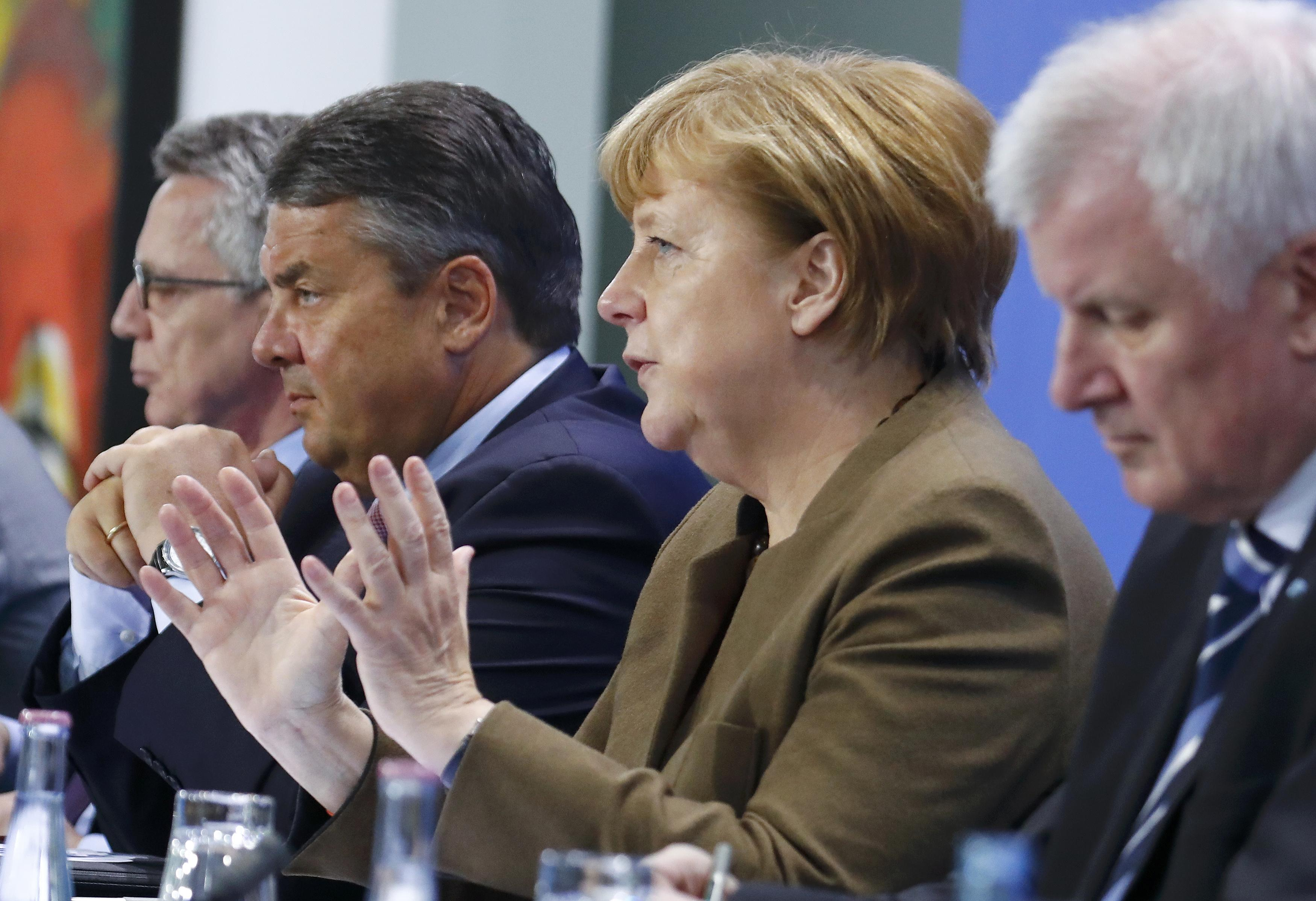 German Chancellor Merkel speaks next her ministers during a news conference at the Chancellery in Berlin