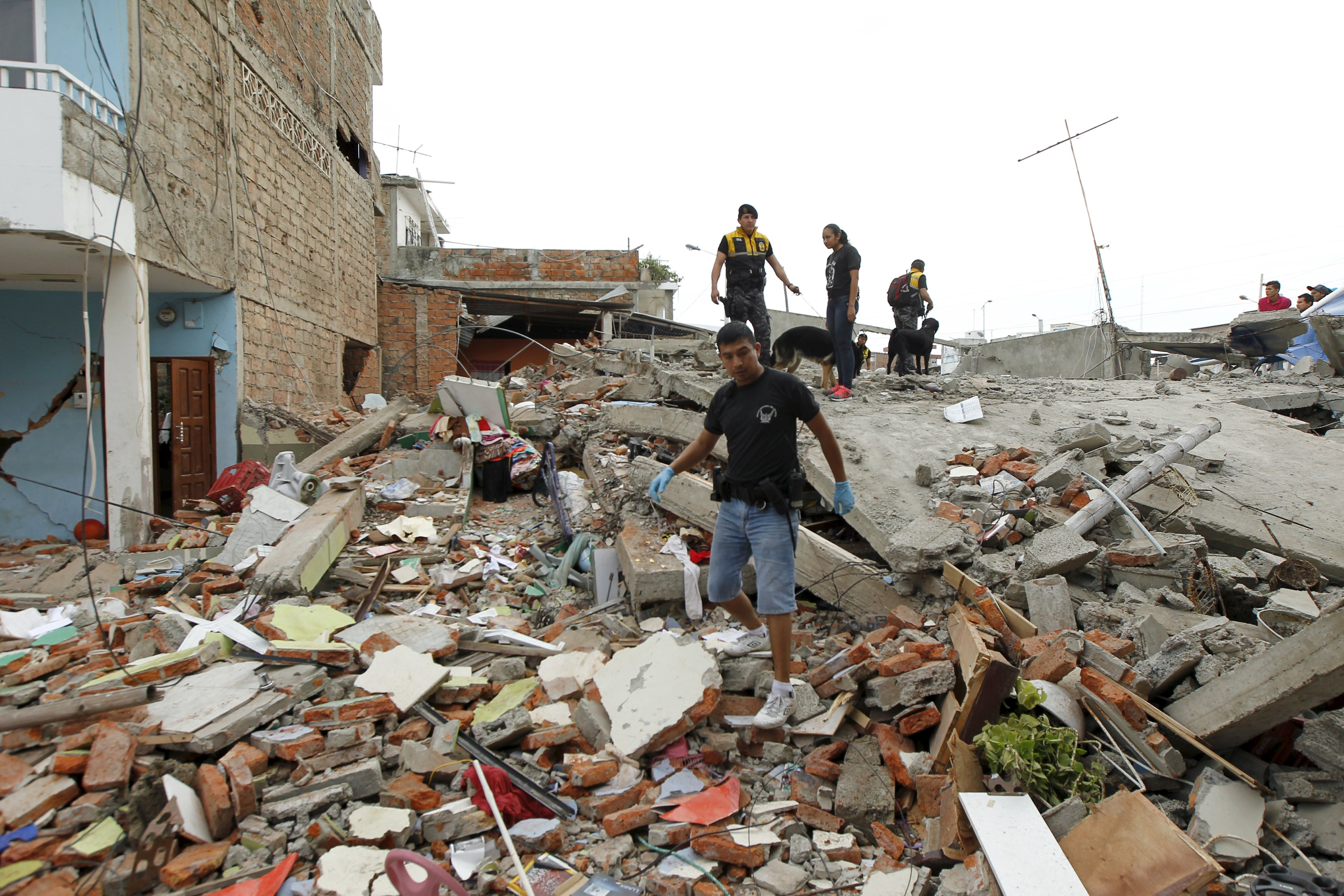 Red Cross members, military and police officers work at a collapsed area after an earthquake struck off the Pacific coast, at Tarqui neighborhood in Manta