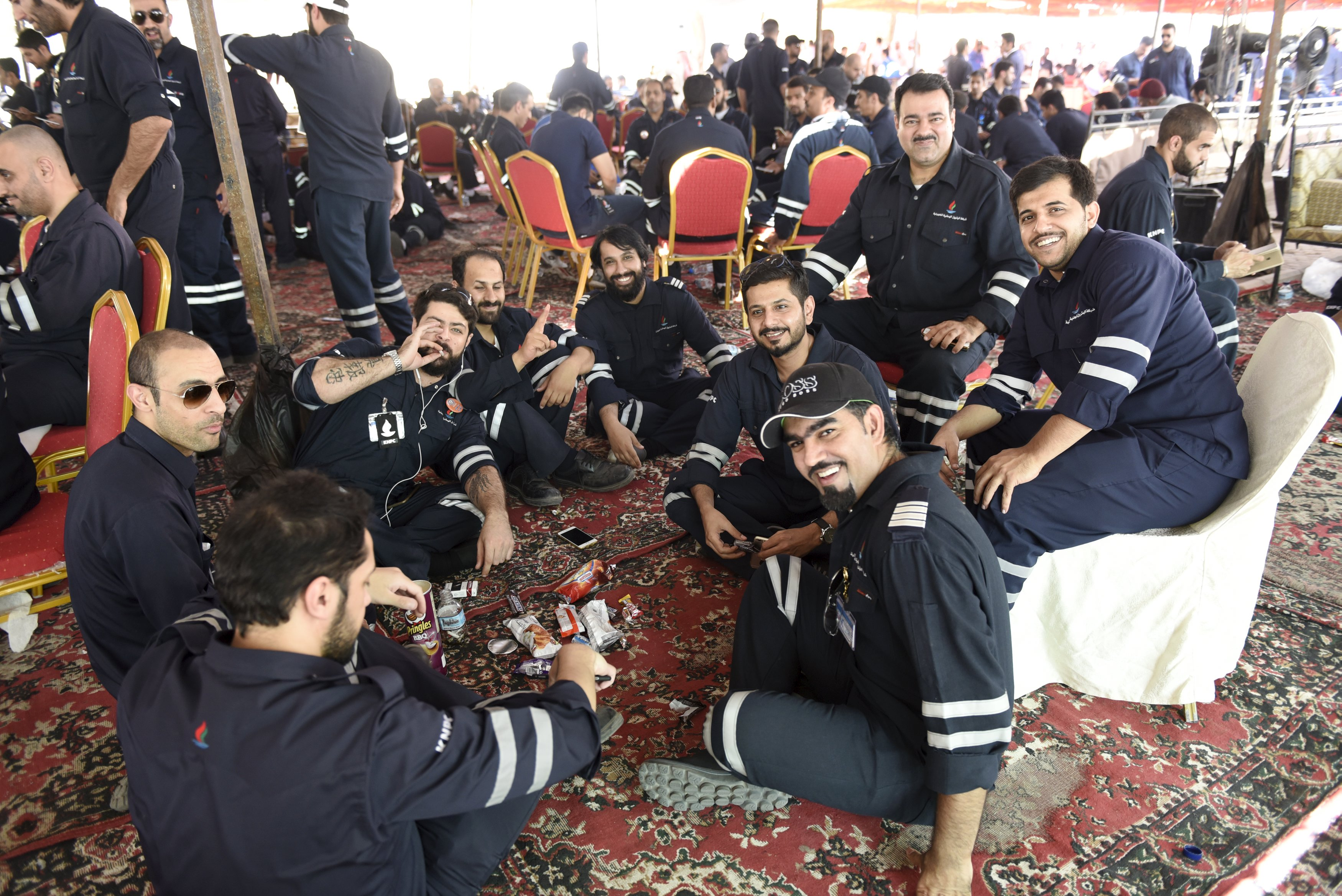 Kuwaiti oil sector employees sit in a shaded area on the first day of an official strike called by the Oil and Petrochemical Industries Workers Union over public sector pay reforms, in Ahmadi