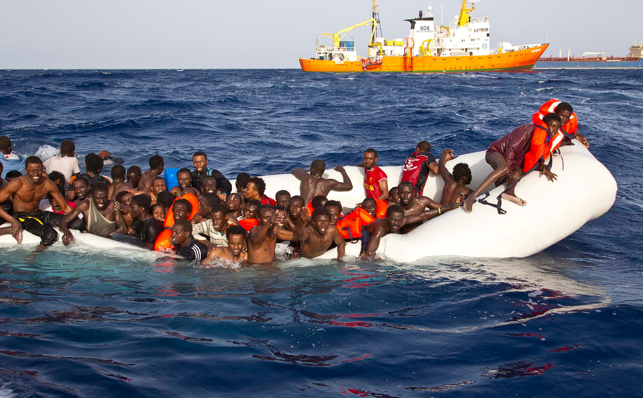 Migrants sit in a rubber dinghy during a rescue operation by SOS Mediterranee ship Aquarius off the coast of the Italian island of Lampedusa