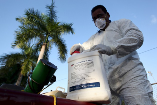 A health worker prepares insecticide before fumigating a neighborhood in San Juan