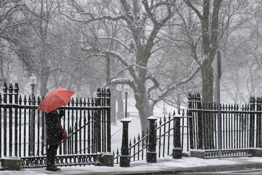 A pedestrian with a red umbrella waits in the snow during a spring snow storm