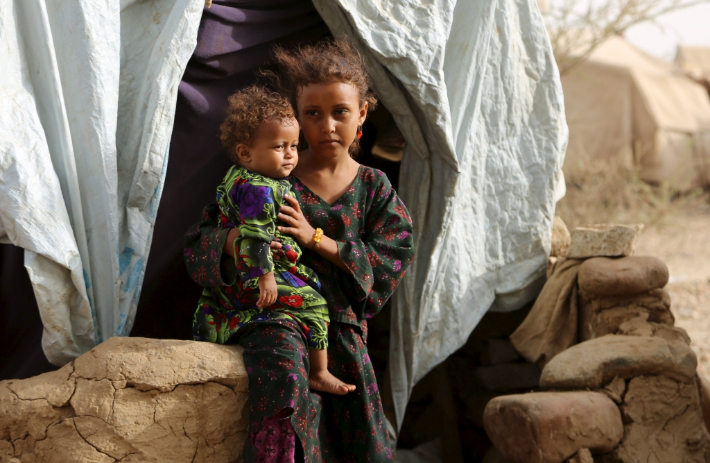 A girl holds her sister outside their family's hut at the Shawqaba camp