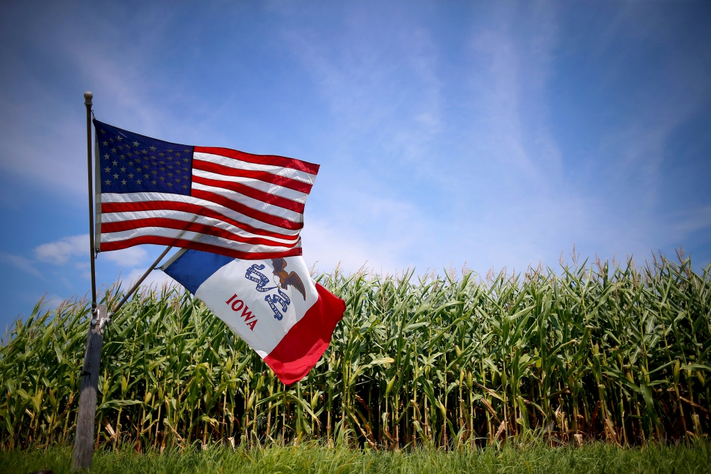 File photo of a U.S. and Iowa state flag are seen next to a corn field in Grand Mound, IOWA