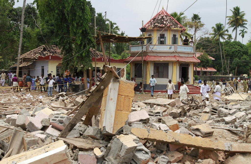 People stand next to debris after a broke out at a temple in Kollam in the southern state of Kerala, India