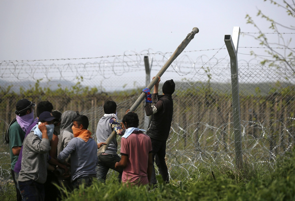 Men try to break a border security fence during scuffles between Macedonian police and migrants and refugees near a makeshift camp at the Greek-Macedonian border near the village of Idome