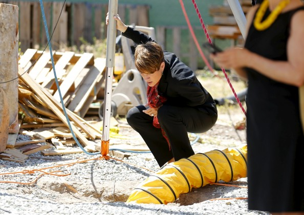 United States attorney Laura E. Duffy looks down the opening of a hole in the ground after the discovery of a cross-border tunnel
