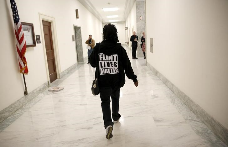 "A woman with a ""Flint Lives Matter"" shirt walks toward a hearing room where Michigan Governor Rick Snyder and EPA Administrator Gina McCarthy will testify on Capitol Hill in"