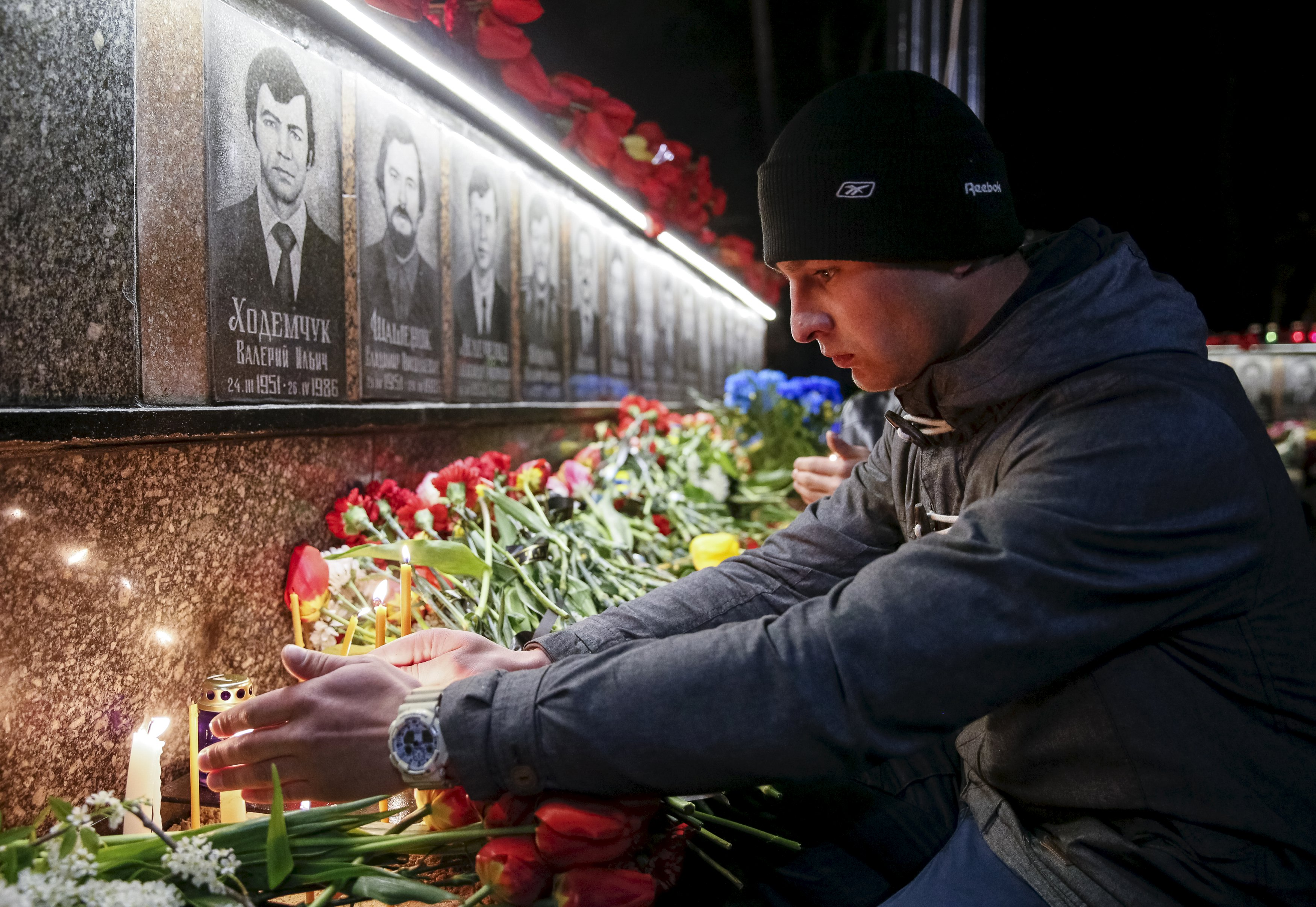 A man lights a candle at a memorial, dedicated to firefighters and workers who died after the Chernobyl nuclear disaster, during a night service in the city of Slavutych