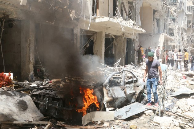 People inspect the damage at a site hit by airstrikes, in the rebel-held area of Aleppo's Bustan al-Qasr