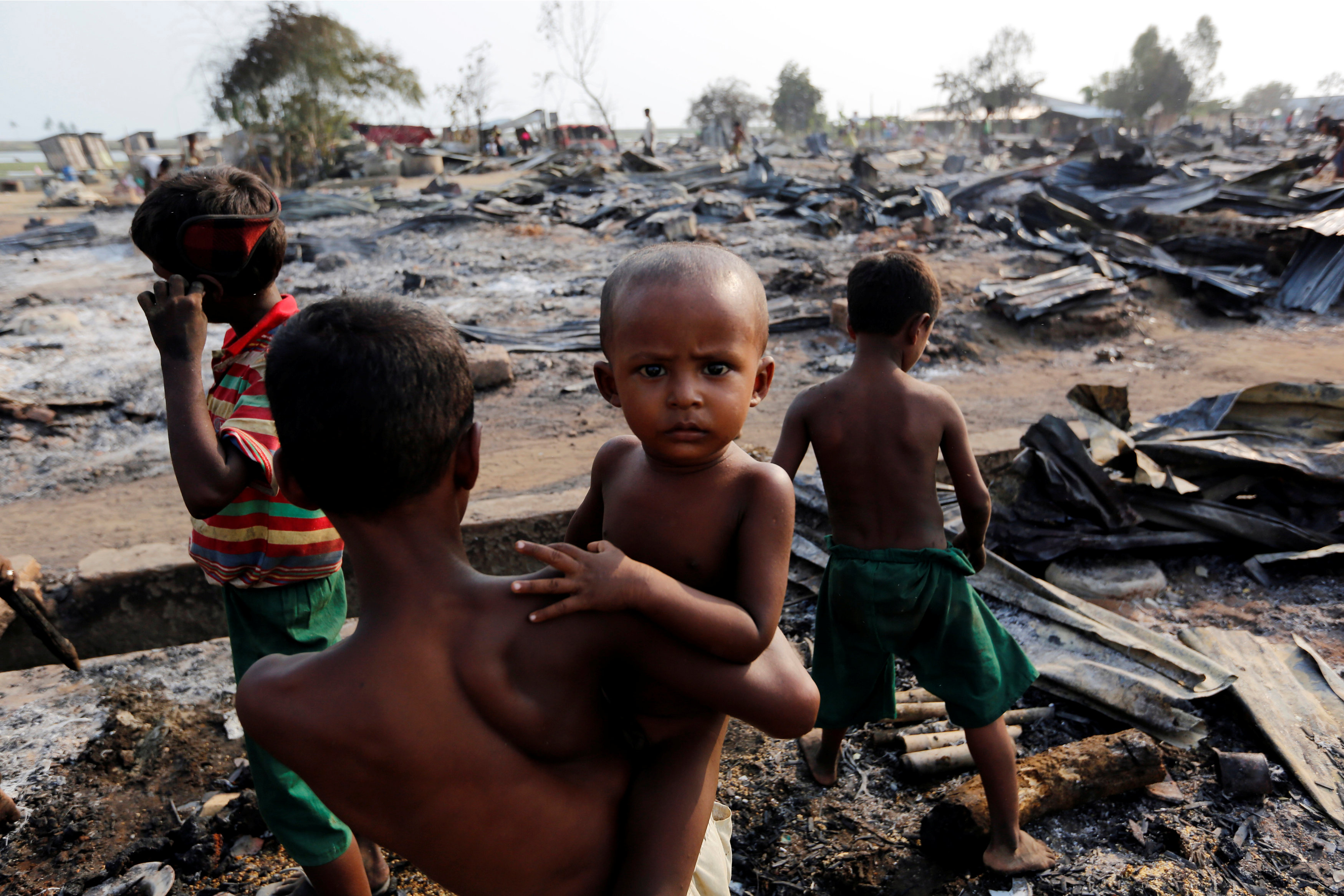 Boys stand among debris after fire destroyed shelters at a camp for internally displaced Rohingya Muslims in the western Rakhine State near Sittwe