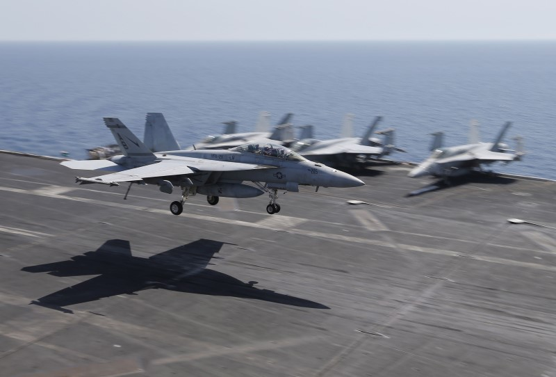A F/A-18E/F Super Hornets of Strike Fighter Attack Squadron 211 (VFA-211) lands on the flight deck of the USS Theodore Roosevelt (CVN-71) aircraft carrier