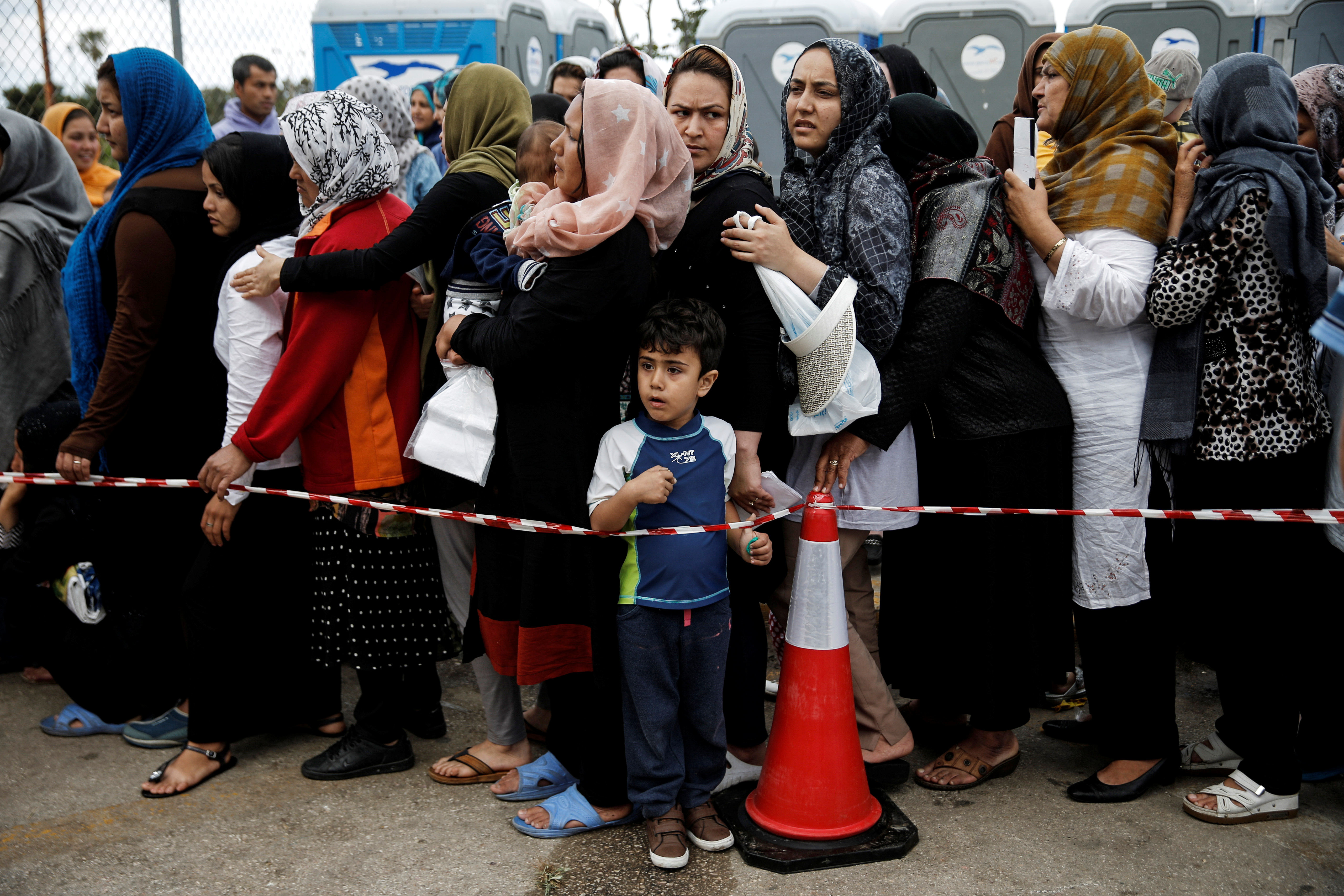 Migrants line up to receive personal hygiene goods distributed by the United Nations High Commissioner for Refugees (UNHCR), outside the main building of the disused Hellenikon airport
