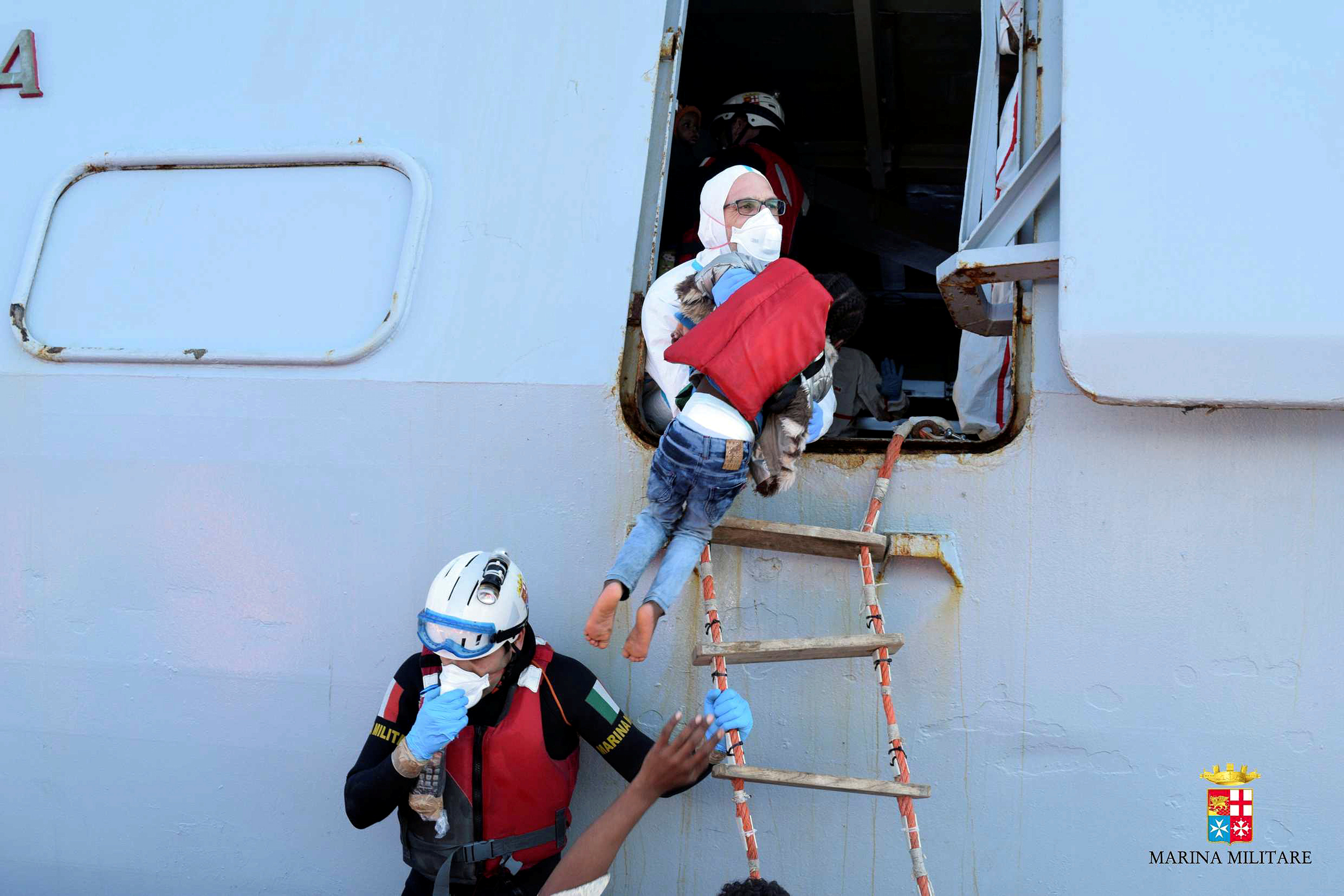 A child is helped during a rescue operation by Italian navy ship Grecale off the coast of Sicily