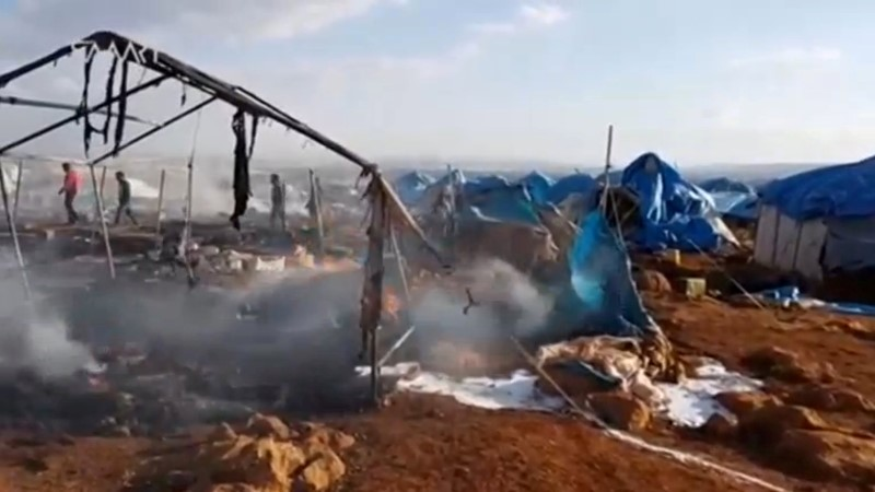 People walk though burned tents at a camp for internally displaced people near