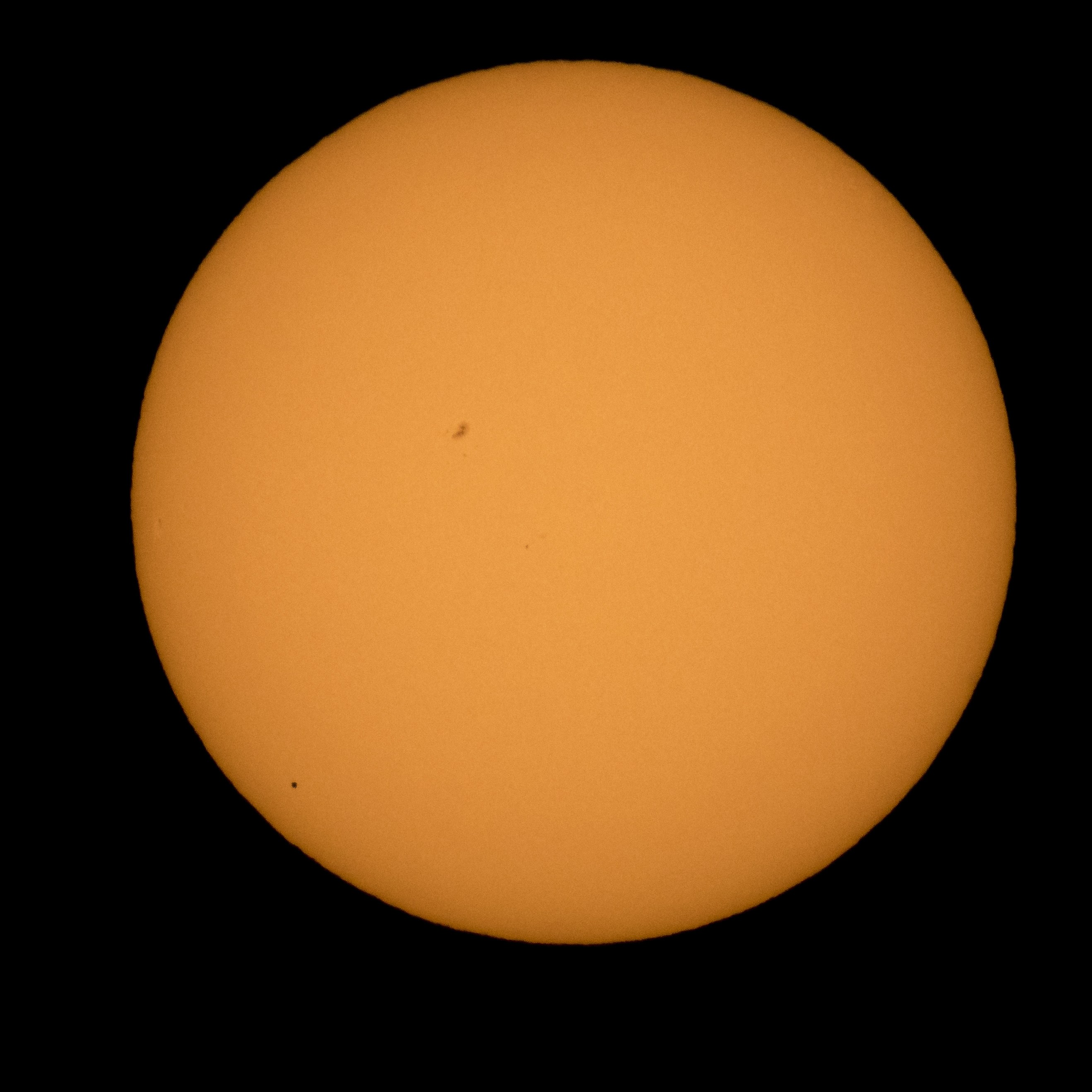 The planet Mercury is seen in silhouette lower left as it transits across the face of the sun