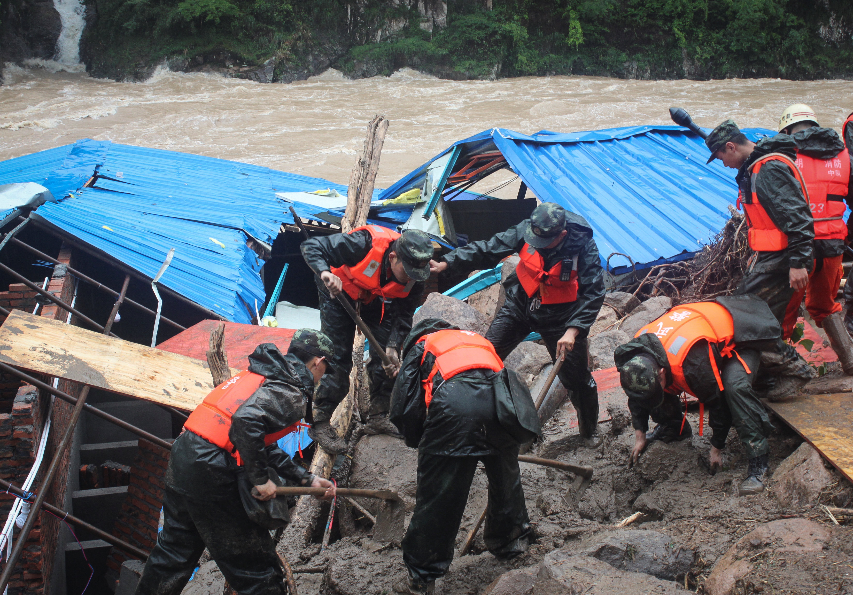 Paramilitary policemen search for missing people at the site of a landslide in Sanming