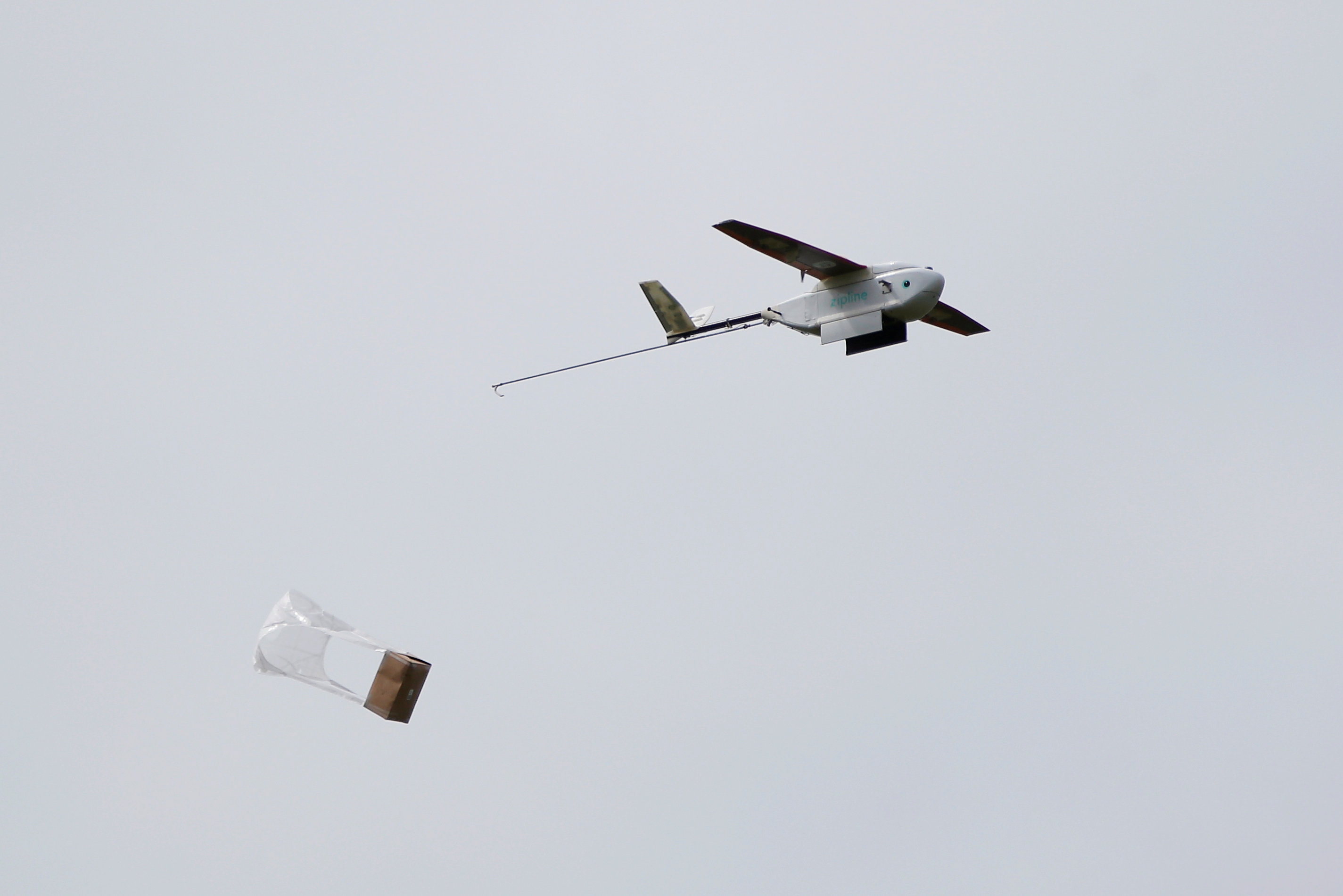 A Zipline delivery drone releases its payload midair during a flight demonstration at an undisclosed location in the San Francisco Bay