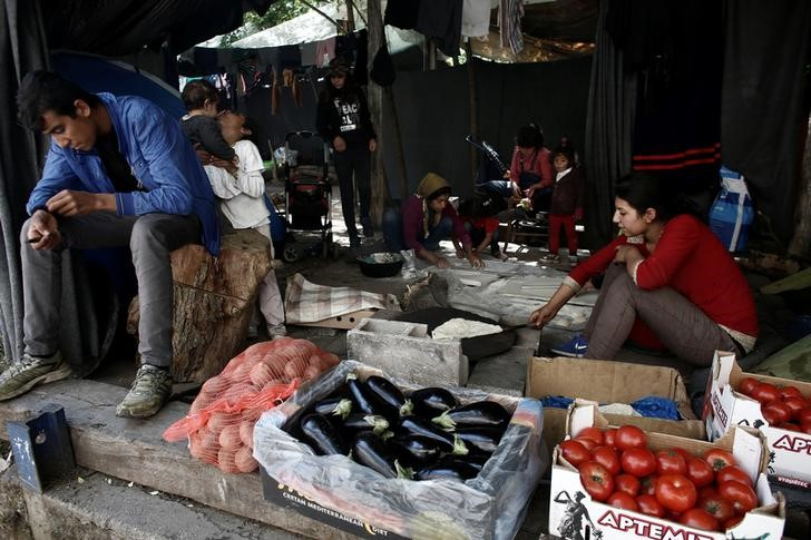 A refugee sits by his grocery stall as women cook traditional Arabic bread at a camp for refugees and migrants at the Greek-Macedonian border near the village of Idomeni, Greece,
