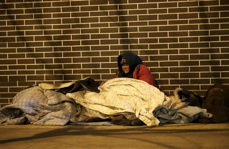 A homeless woman is seen on a cold winter night near Beijing South Railway Station in Beijing