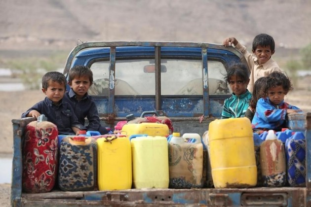 Children ride on the back of a truck loaded with water jerrycans at a camp for internally displaced people in the Dhanah area of the