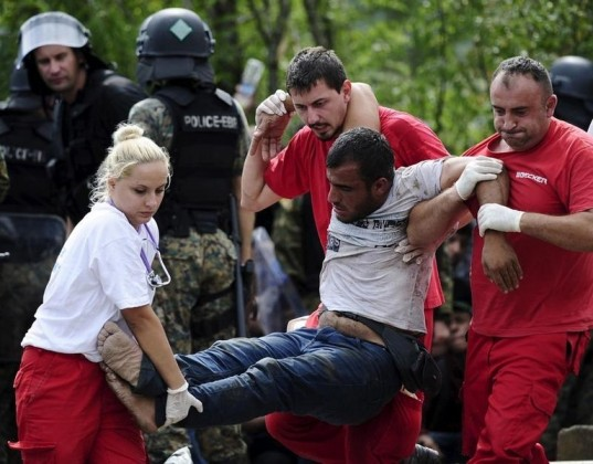 Red Cross workers assist a collapsed migrant after he crossed Greece's border with Macedonia, in