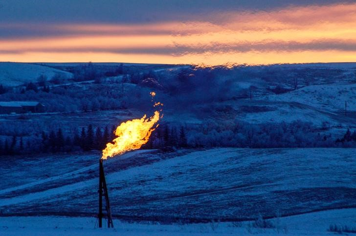 A natural gas flare on an oil well pad burns as the sun sets outside Watford City,