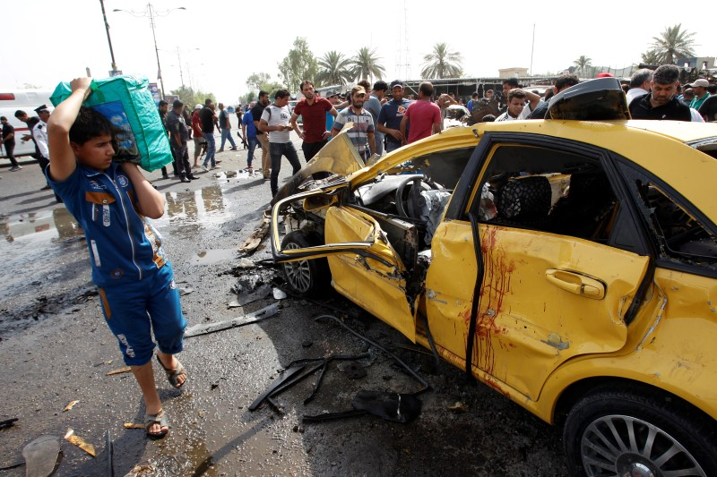 People gather at the site of a car bomb attack in Baghdad's mainly Shi'ite district of Sadr City, Iraq, May 17, 2016.