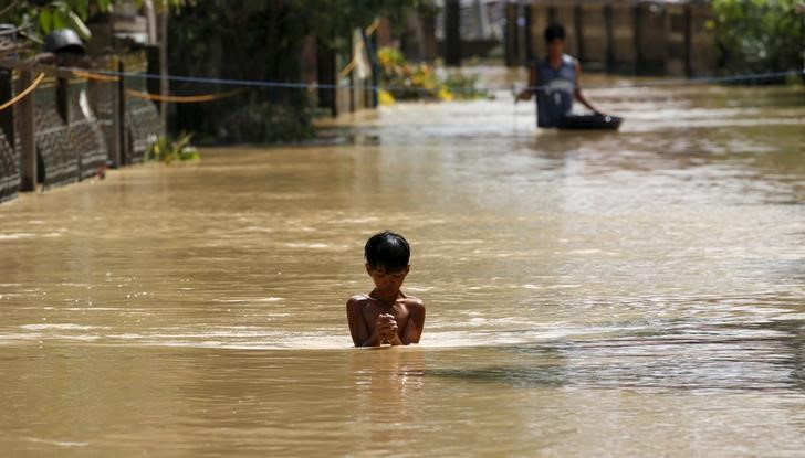 A boy wades through a flooded street in Jaen, Nueva Ecija in northern Philippines October 20, 2015, after the province was hit by Typhoon Koppu.