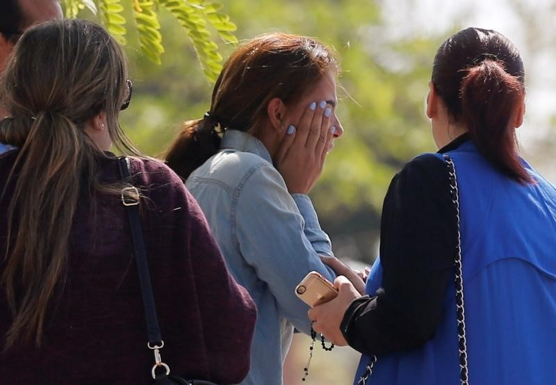 Unidentified relatives and friends of passengers who were flying in an EgyptAir plane that vanished from radar en route from Paris to Cairo react as they wait outside the Egyptair in-flight service building where relatives are being held at Cairo International Airport, Egypt