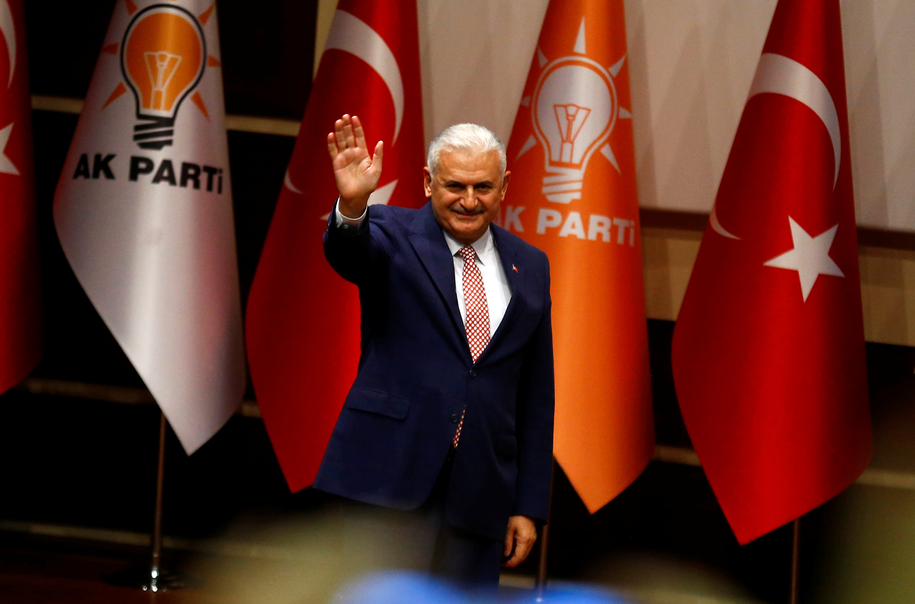 Turkey's likely next prime minister and incoming leader of the ruling AK Party Binali Yildirim greets party members during a meeting in Ankara