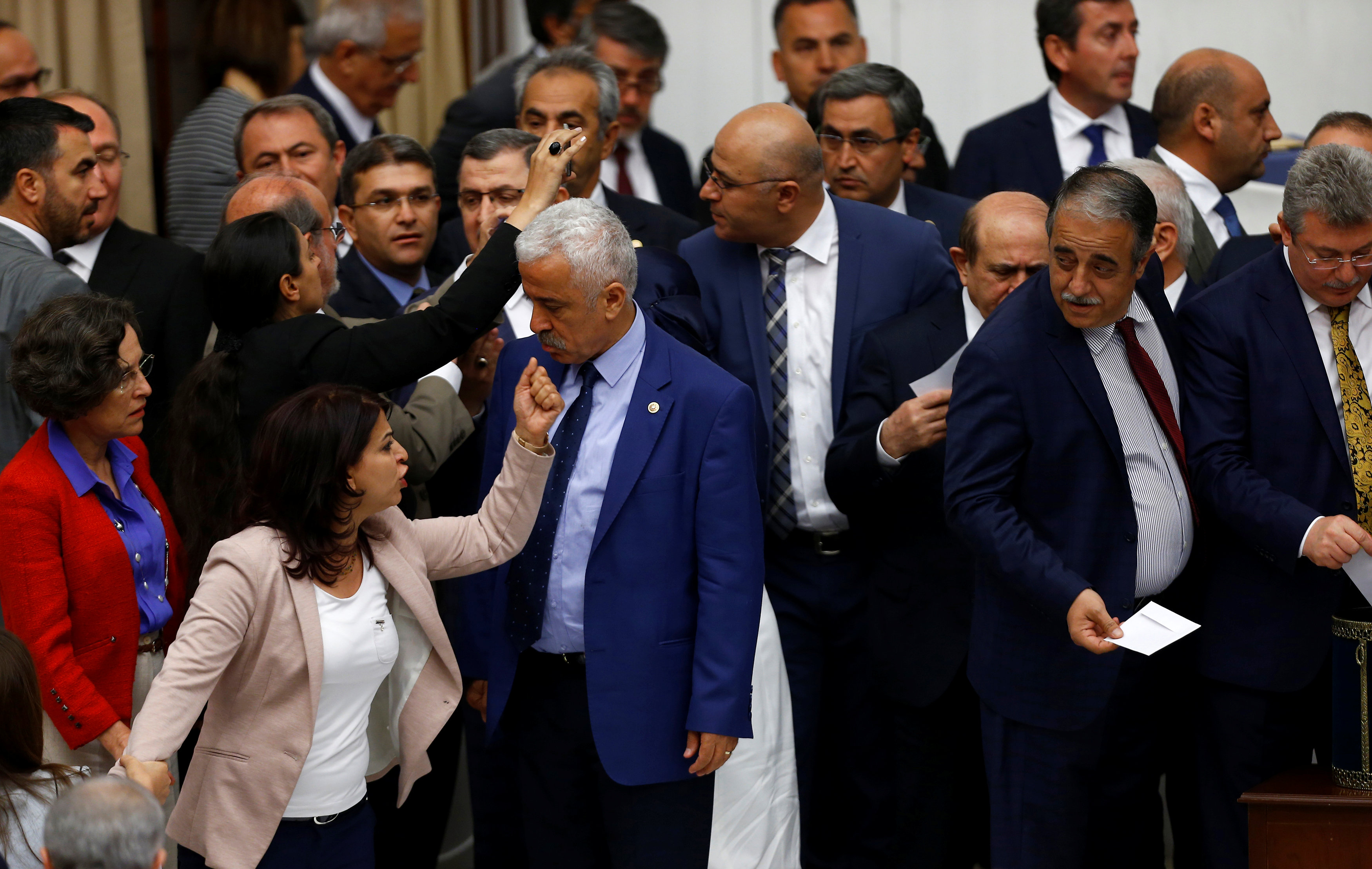 Pro-Kurdish opposition Peoples' Democratic Party (HDP) MPs react to Turkey's ruling AK Party (AKP) as they vote in favor of an article of constitutional change that could see pro-Kurdish and other lawmakers prosecuted at the Turkish parliament in Ankara, Turkey, May 20, 2016.