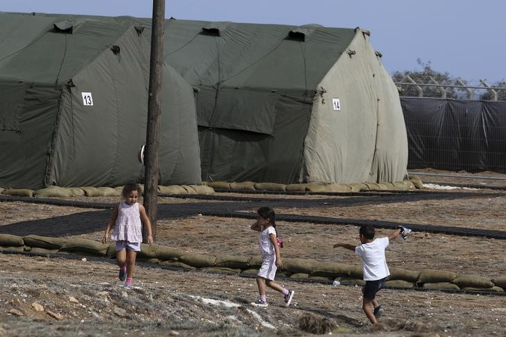 Refugees and migrants children interact with each other at a temporary transit facility at the British sovereign base of Dhekelia in Cyprus