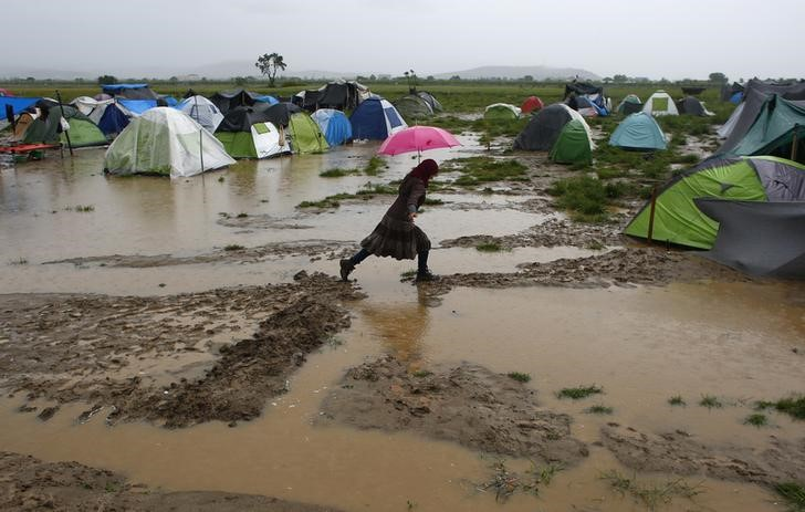 A woman holding an umbrella walks in a flooded field during heavy rainfall at a makeshift camp for refugees and migrants at the Greek-Macedonian border