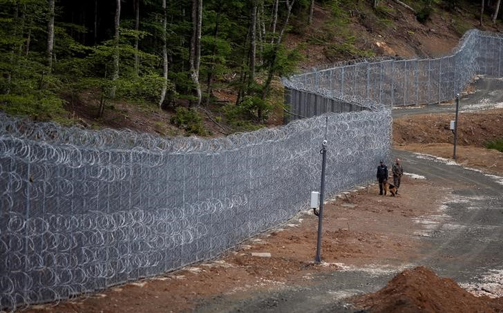Bulgarian border policemen stand guard near barbed wire fence constructed on the Bulgarian-Turkish border, near Malko Tarnovo