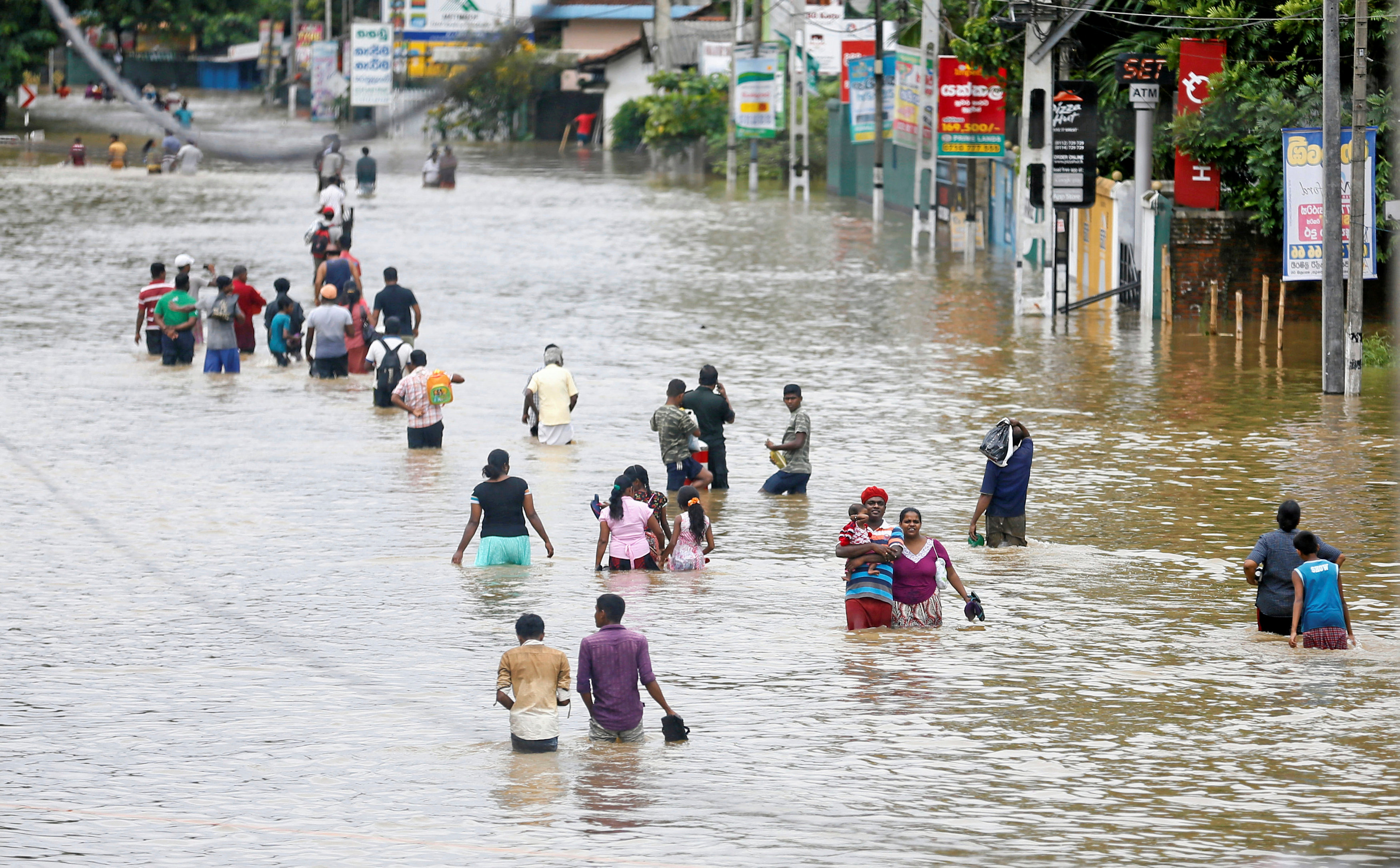 People walk through a flooded road after they moved out from their houses in Biyagama