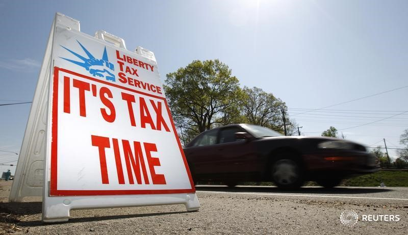 A car passes a sign advertising tax return services in Falls Church, Virginia