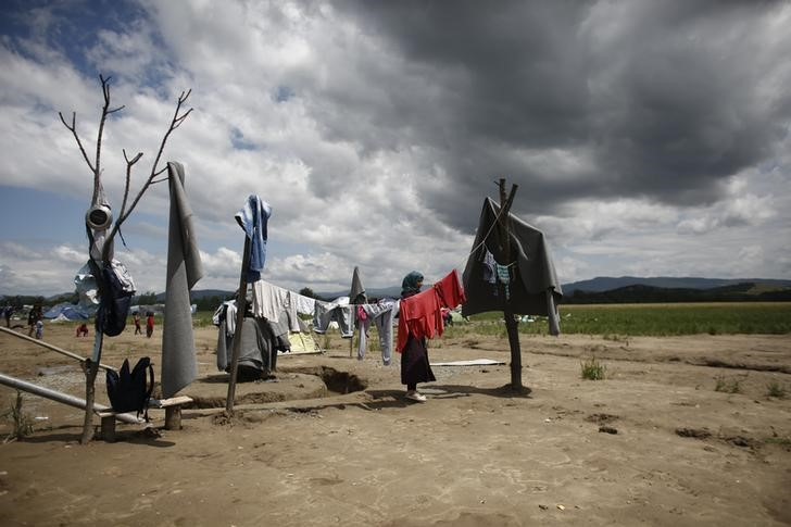 A refugee woman hangs clothes to dry at the sun after heavy rainfall at a makeshift camp for migrants and refugees near the village