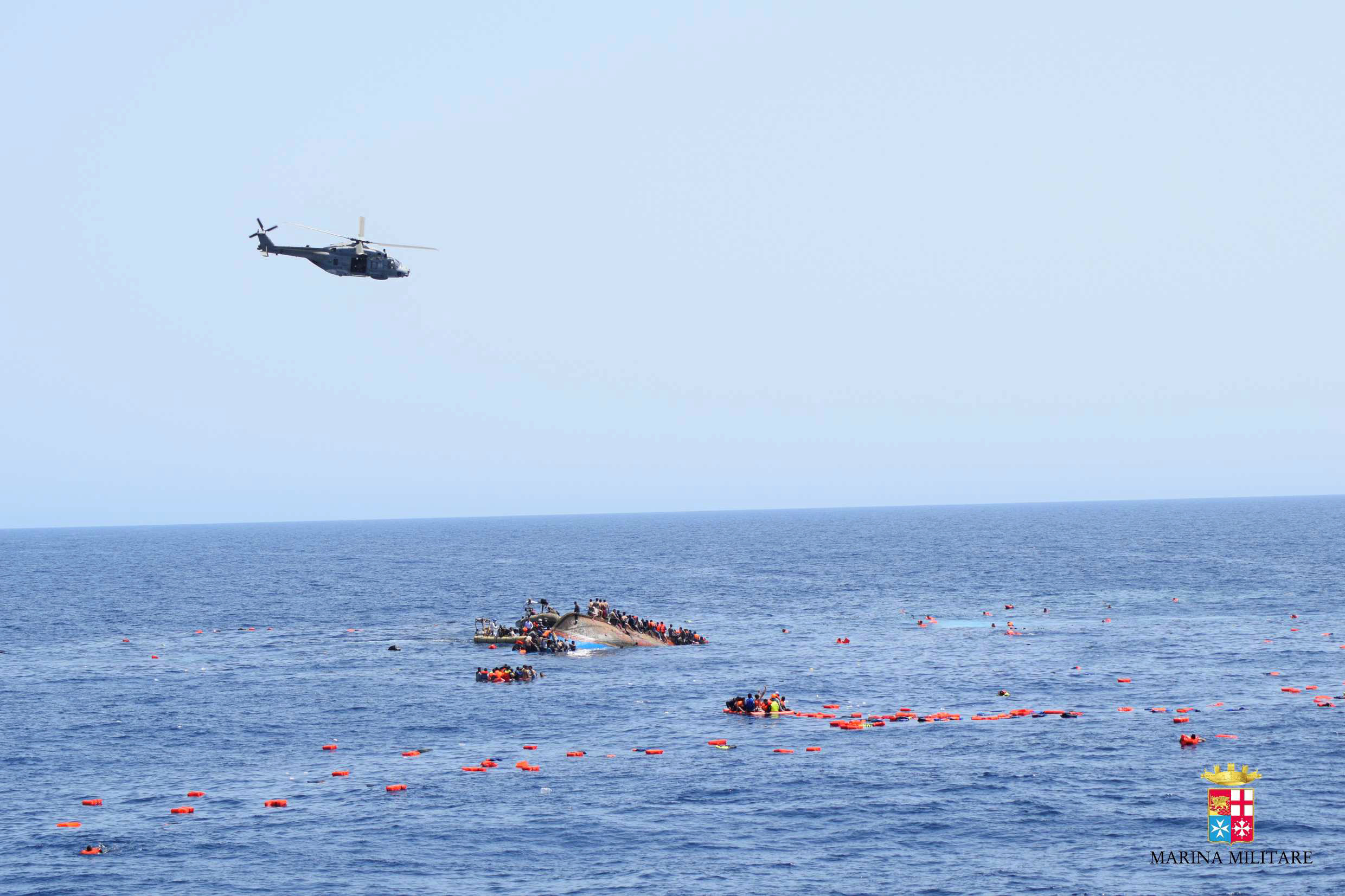 """Migrants from a capsized boat are rescued during a rescue operation by Italian navy ships """"Bettica"""" and """"Bergamini"""" off the coast of Libya"""