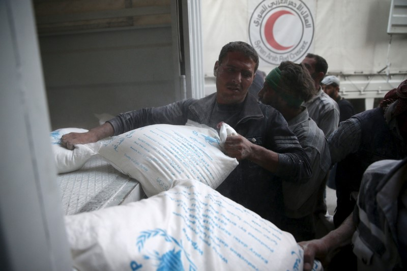Men unload flour from a Red Crescent and United Nations aid convoy in the rebel held besieged town of Hamoria area in Syria
