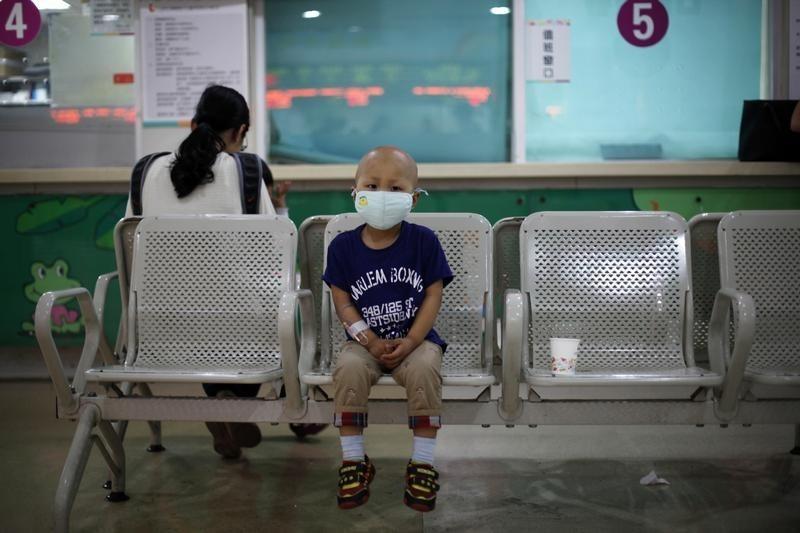 Four-year-old Niuniu sits on a bench while his mother pays his medical bills at Shanghai Children's Hospital
