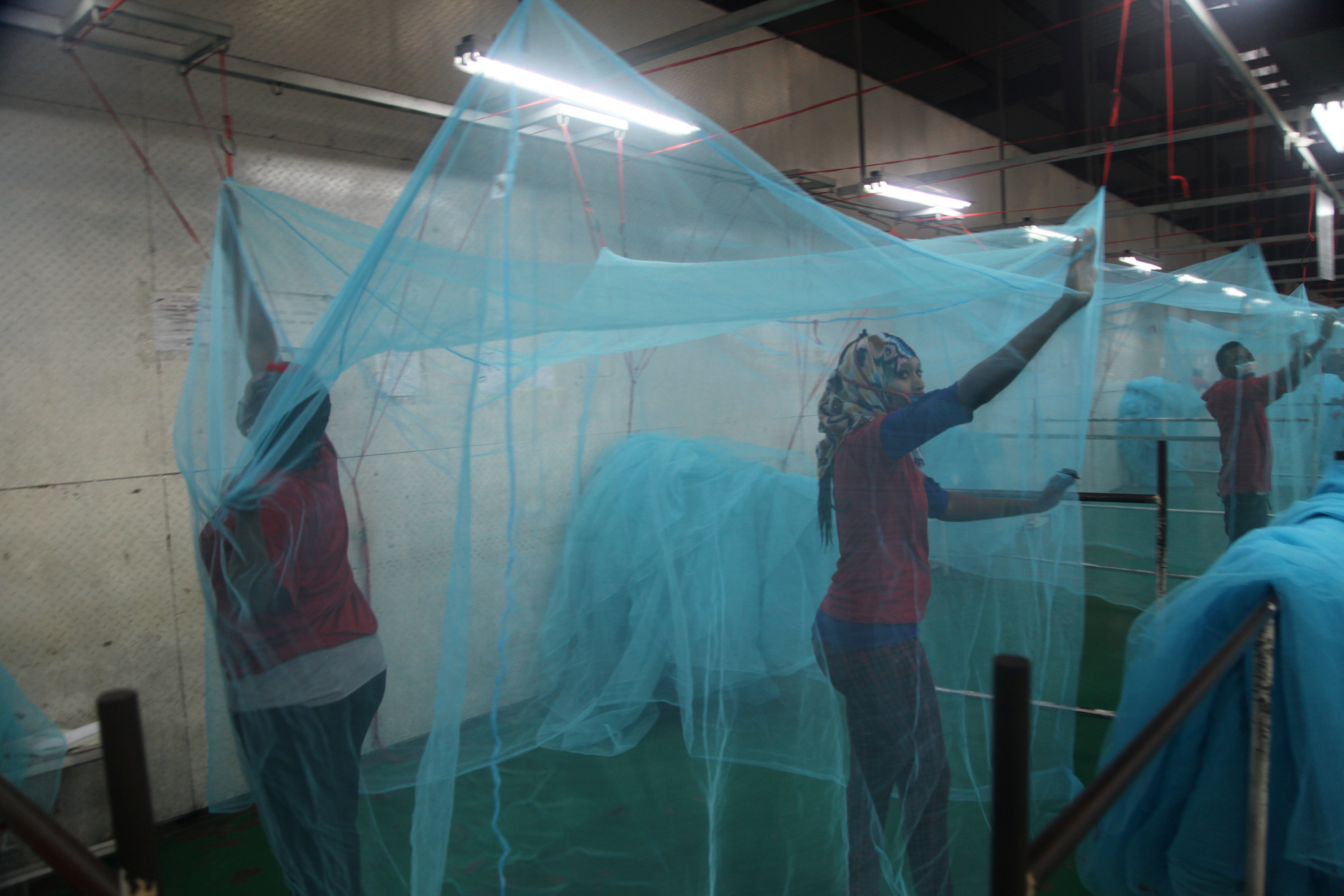 Workers look for holes in mosquito netting at the A to Z Textile Mills factory producing insecticide-treated bednets in Arusha, Tanzania