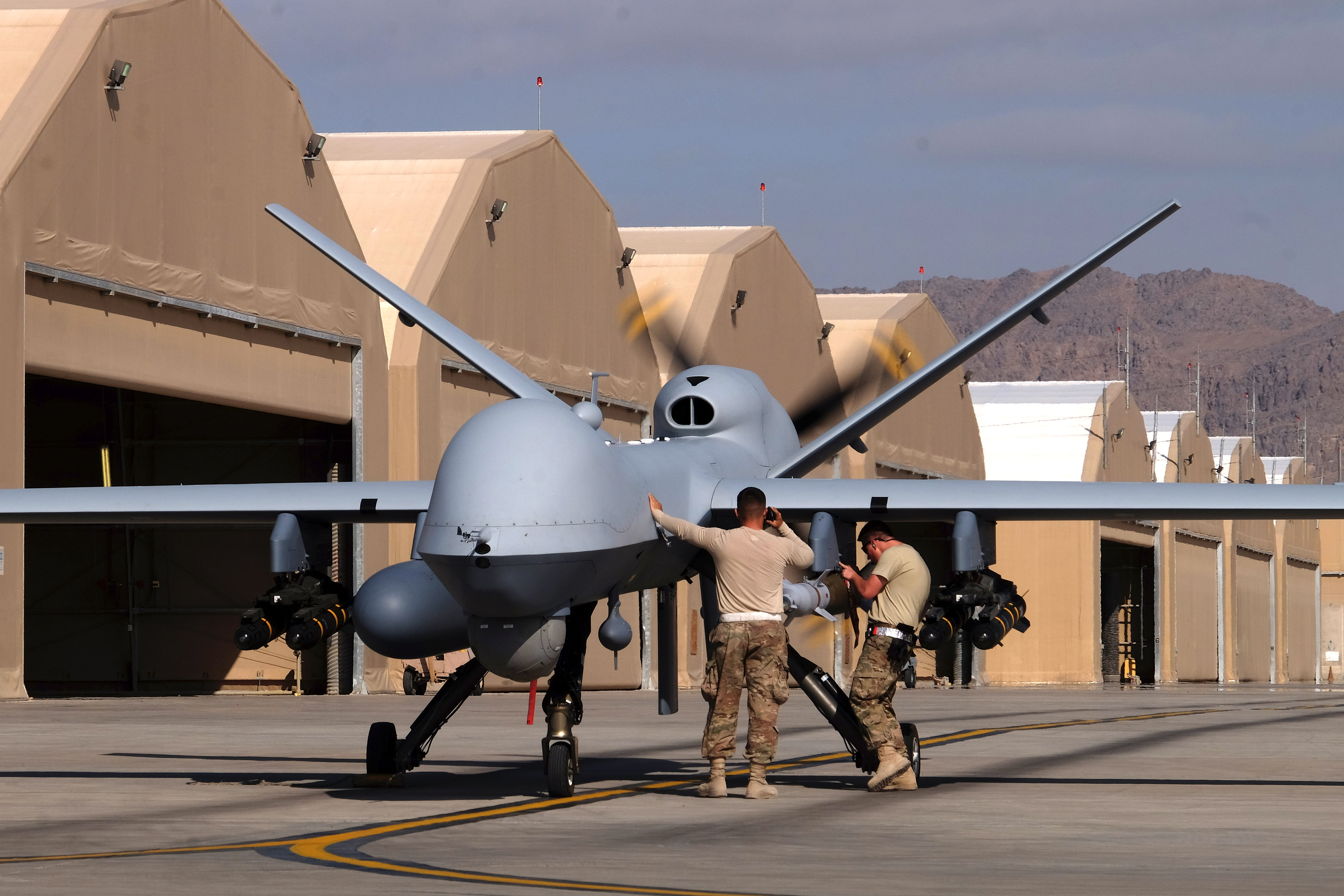 U.S. airmen prepare a U.S. Air Force MQ-9 Reaper drone as it leaves on a mission at Kandahar Air Field