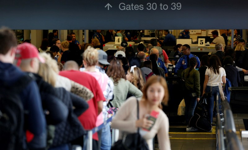 Travelers stand in line to go through Transportation Security Administration (TSA) check-points at Los