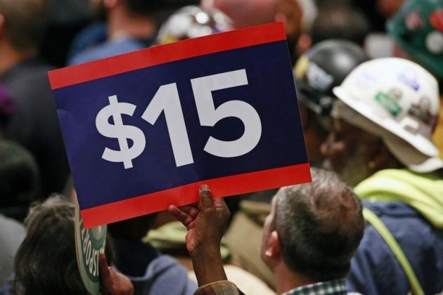 A supporter holds a sign aloft while listening to U.S. Democratic presidential candidate Clinton during a rally to celebrate the state of New York passing into law a $15 minimum wage in New York