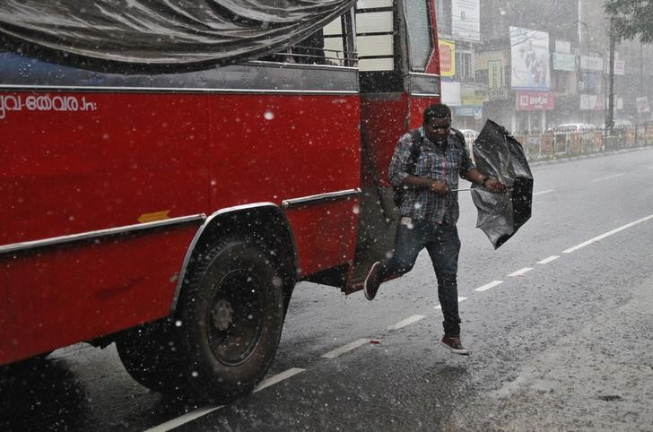 A commuter jumps from a bus during a heavy rain shower at a bus stop in Kochi