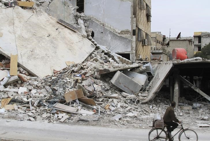 A man rides a bicycle past a damaged building in Daraya, near Damascus