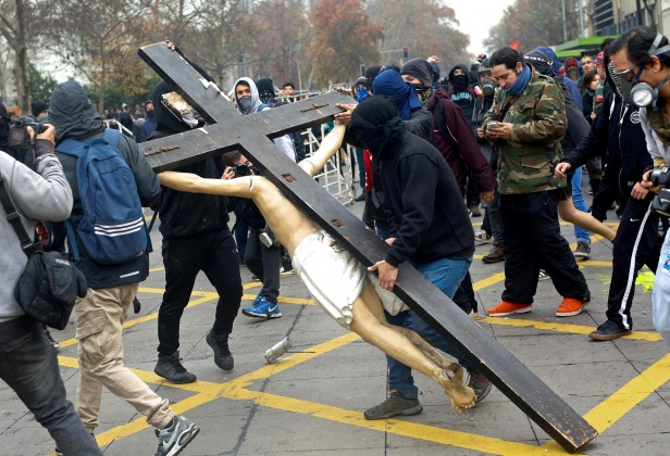 Masked demonstrators carry a cross with Jesus Christ during a protest against government education reforms in Santiago