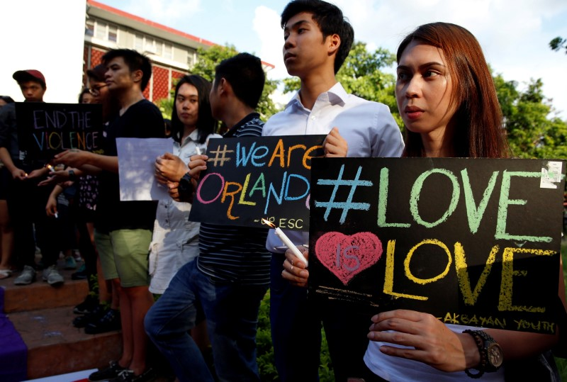 University of the Philippines students hold lit candles and placards as a tribute to those killed in the Pulse nightclub mass shooting in Orlando,