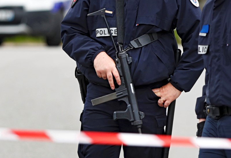 Police at the scene where a French police commander was stabbed to death in front of his home in the Paris